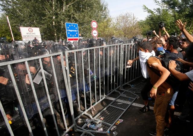 """Se lanzan """"amistosamente"""" """"a pedir socorro"""" los """"corderitos"""" """"buena gente"""", para lo cuál se cubren el rostro como las moras; con """"pataditas"""" descuajaringan la reja de la frontera húngara, y .... (AP Photo/Darko Vojinovic)"""